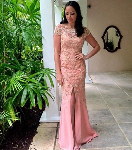 Luciana Tranchesi veste Trinitá para o casamento de Mica Rocha e Renato Mimica nas Bahamas. O vestido longo cor pêssego tem fenda frontal e é cheio de aplicações de renda.