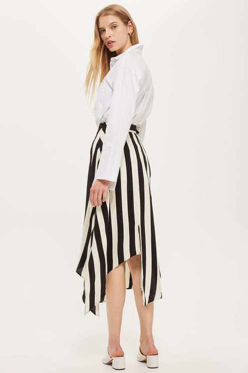 In bold unapologetic, monochrome stripes, this hanky hem midi skirt is a statement daytime style. Featuring a front split, high waist and sash detail, wear it with a crisp white shirt tucked in.
