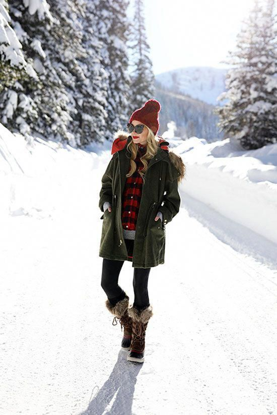 5 Stylish Snow Outfit Ideas: Fashion blogger Atlantic-Pacific wearing a red pom pom beanie, a military parka, a red plaid shirt, a grey tunic sweater, black leggings, brown snow boots and black cat eye sunglasses. Casual outfit, snow outfit, snow day outfit, winter outfit, rain day outfit, comfy outfit, skiing trip outfit, cold weather outfit, cozy outfit, winter layers. #VersalisSolidWomensraincoat