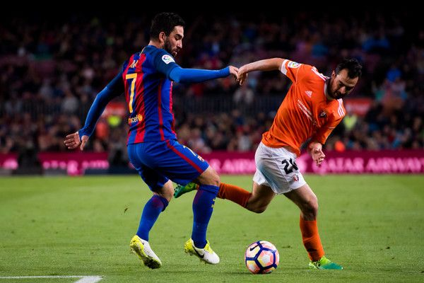 Arda Turan (L) of FC Barcelona competes for the ball with Miguel Angel De las Cuevas of CA Osasuna during the La Liga match between FC Barcelona and CA Osasuna at Camp Nou stadium on April 26, 2017 in Barcelona, Catalonia.