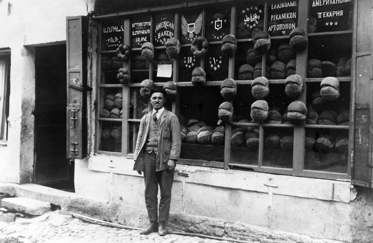 """Baker standing in front of the """"American Bakery"""" which displays signs in Armenian, Ladino (in Hebrew characters), English, Ottoman Turkish, Greek and Russian with samples of bread attached to the mullions, Ortaköy, Istanbul, Turkey. 1922 June."""