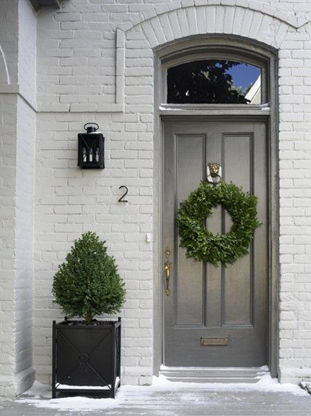 Simple. Elegant. Welcoming. I love the two tones of grey in the exterior, a touch of black in the lantern and a pop of color and life with the greenery.: