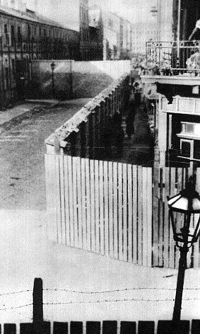 "On October 2, 1940, the Warsaw ghetto was formally established. Six weeks later, on November 15, the ghetto was sealed with walls, as shown in this 1941 photograph. ""Ghettoization"" restricted the rights of Jews, created deplorable living conditions, and clustered Jews into condensed areas facilitating the eventual deportations to extermination camps."
