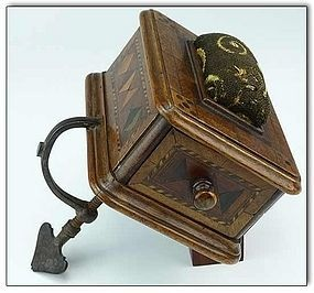 ca1850. . Antique Tunbridge Ware sewing box attached to an adjustable clamp (with heart shaped screw)  with a patterned old woven pincushion on top.