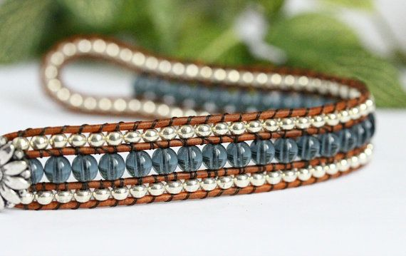 This beaded leather cuff features 3 rows of glass beads and genuine leather. Metallic silver seed beads surround a center row of denim blue. Each bead is hand stitched between rows of distressed light brown leather. For a touch of country charm this bracelet fastens easily with a daisy button clasp. Fits up to a 6 1/2 wrist. Measures 7 1/2 and 3/4 wide. If you would like me to make this bracelet in another size for you, please leave your wrist size in the Notes to Seller box at the checkout…