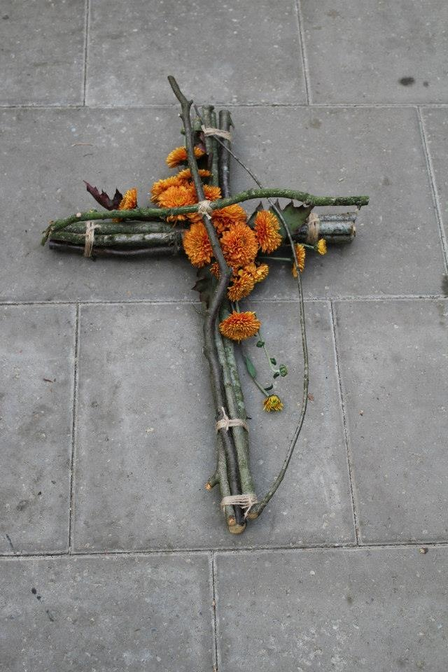 Cross of branches with brown chrysanthemums - funeral arrangement -