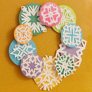 Use your own hand-cut paper snowflakes glued to colored circles.