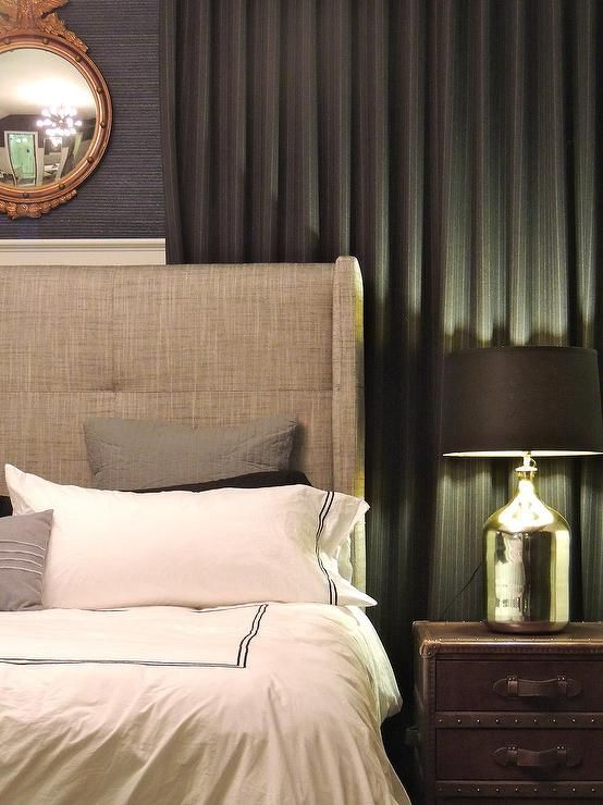 Masculine bedroom features a gilt mirror over a gray linen wingback bed dressed in black and white stitched duvet and shams as well as gray pillows next to a leather steam trunk nightstand topped with a mercury glass lamp accented with a black shade place din front of window dressed in a black pinstripe curtain.