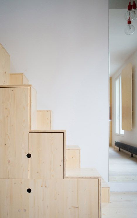 Apartment in Paris by Schemaa features a staircase made of cupboards.