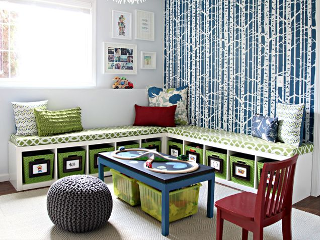 created a cheery, sophisticated playroom with tons of toy storage and seating, thanks to a corner bench made from Expedits. Custom upholstery in a fresh green and white print plays perfectly against the blue birch wall stencils.