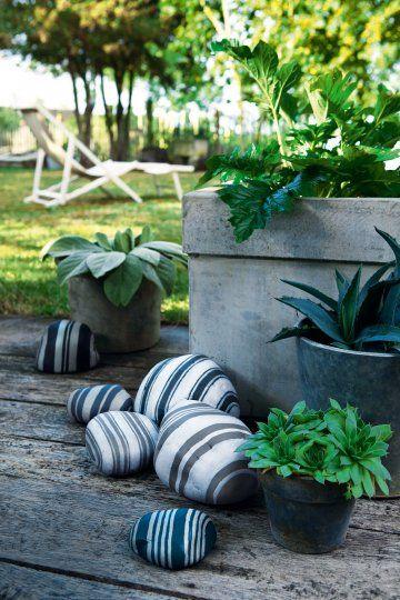Galets peints de rayures bicolores comme une toile à matelas pour décorer le jardin