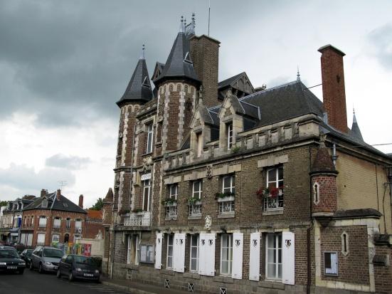 Corbie (Somme, France) - Façade Ouest de la mairie. Rue Faidherbe et son prolongement Rue Marcellin Truquin (vue vers le Nord). Le Monument aux Morts est ici à gauche, au-delà de la Mairie avec ses tourelles. CC BY-SA Markus3 (Marc ROUSSEL)