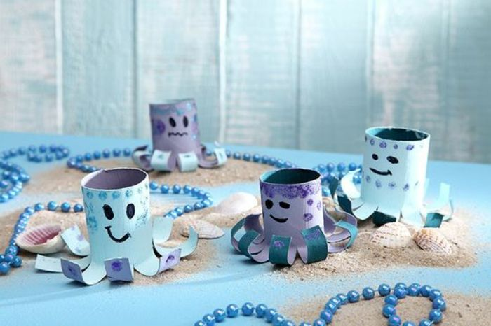 summer crafts, four octopi decorations, made from toilet paper rolls, painted in pale blue and violet, placed on blue surface, with seashells sand and blue beaded ropes