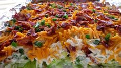 Homemade Seven Layer Salad Recipe - shredded lettuce, celery for crunch, tasty mayo dressing mixture and topped with cheese and bacon.