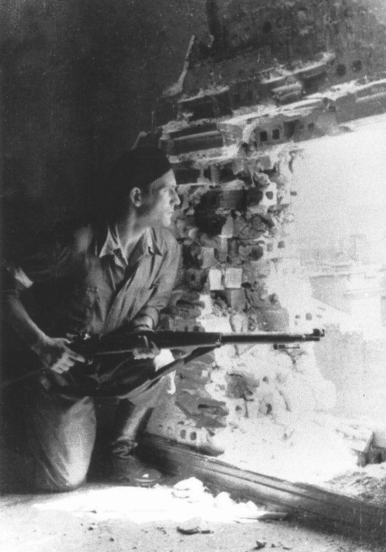 Польский повстанец ведет наблюдение через пролом в стене
