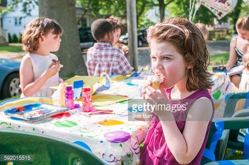 Stock Photo : Young girl eating ice cream at kindergarten party