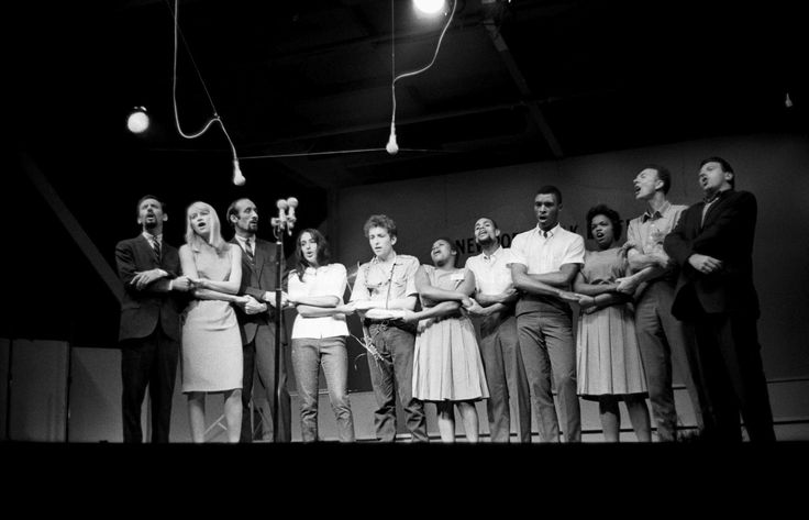 "Peter, Paul and Mary, Joan Baez, Bob Dylan, the Freedom Singers, Pete Seeger, and Theodore Bikel photographed on July 26, 1963, by John Byrne Cooke at the Newport Folk Festival, singing ""We Shall Overcome"" with a standing audience of 13,000 joining in."