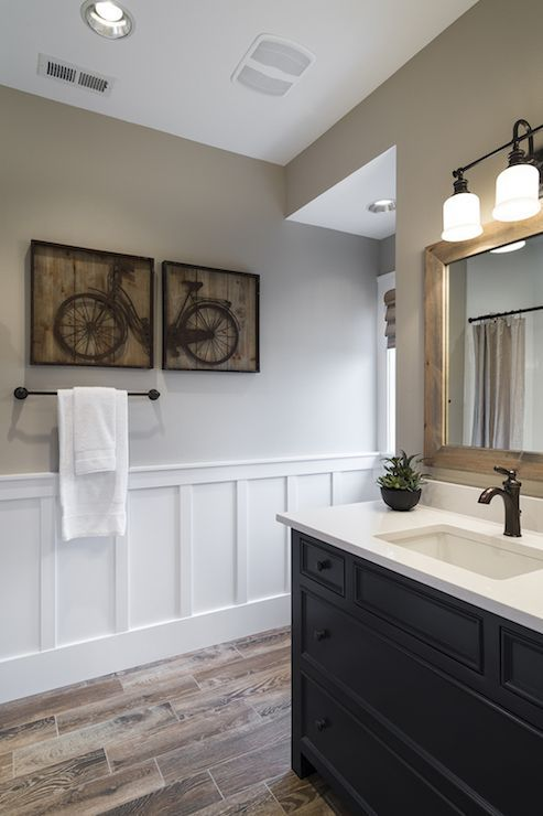 Beautiful bathroom features taupe paint on upper walls adorned with wood planked bicycle art over lower walls clad in board and batten atop wood effect tiled floors. A built-in navy vanity painted Benjamin Moore Old Navy completes the space