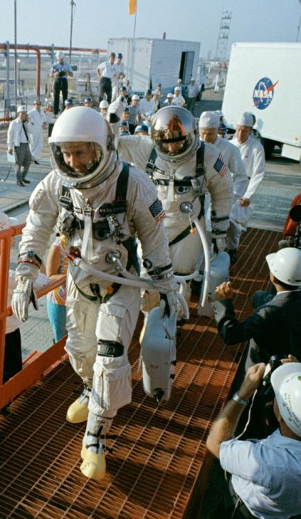 """June 3, 1965 Gemini IV astronauts James McDivitt and Edward White walk towards Pad 19 at Cape Canaveral. Note that Mc Divitt wore an Omega Speedmaster chronograph on each wrist, while Edward """"Ed"""" White wore a pair of Omega Speedmaster 105.003-64 chronographs on his left forearm. The Gemini IV astronauts were the first to wear an American flag on the shoulder of their spacesuit. (Photo: NASA)"""