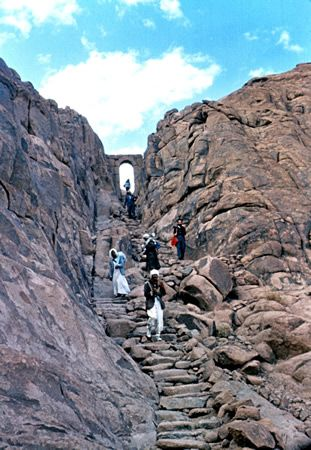 """Stone steps leading to the peak of Mt. Sinai (Jebel Musa) Villagers climb down the 3,750 """"steps of penitence"""" that descend from the """"Arch of St. Stephen,"""" a sixth-century symbolic gate that leads to the sacred area on the peak of Mt. Sinai. The hermitage of Prophet Elijah is in the vicinity."""