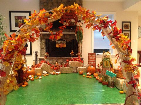 """We bought a """"wedding arch"""" from Michaels and decorated it with burlap and artificial leaves to make the entrance to the indoor pumpkin patch."""