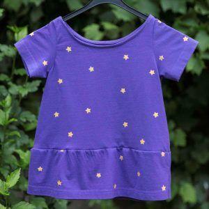 Paars T-shirt met gouden sterretjes. De sterretjes zijn gezeefdrukt.