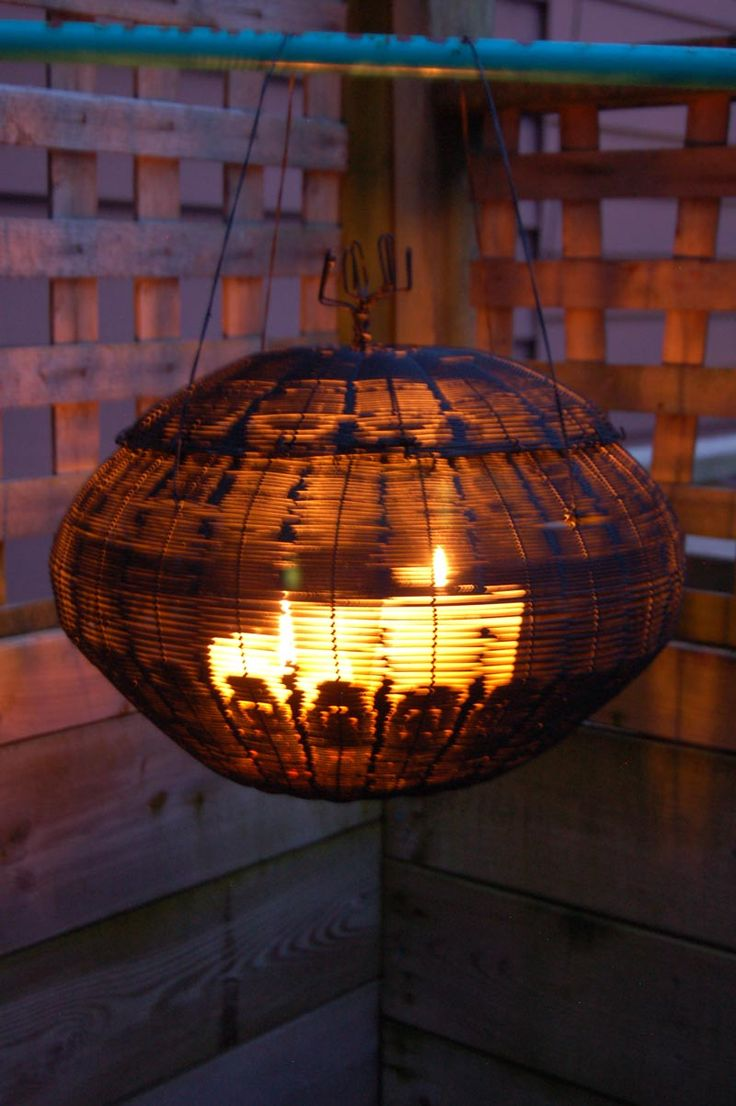 Rustic wire garden lantern re-purposed from a traditional fish-smoking basket.