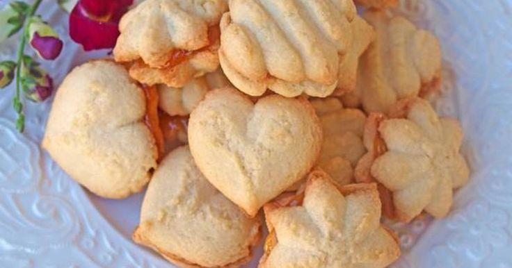 Εξαιρετική συνταγή για Υπέροχα μπισκότα με μαρμελάδα. Αφράτα και μυρωδάτα, λιώνουν απολαυστικά στο στόμα!  Λίγα μυστικά ακόμα  Η ζύμη πρέπει να είναι αφράτη και μαλακιά για να μπορέσουμε να χρησιμοποιήσουμε τη πρέσα.Η δόση βγάζει πάρα πολλά μπισκότα (είχα χάσει το μέτρημα!) γι΄ αυτό είχα φυλάξει τη μισή ζύμη στη κατάψυξη.Αν έχετε τη μαρμελάδα στο ψυγείο, ζεστάνετε την λίγο πρώτα για να μπορέσετε να την απλώσετε πιο εύκολα.Διατηρείστε τα μπισκότα εκτός ψυγείου σε δοχείο που κλείνει…