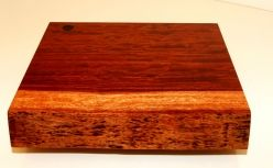 Solid cutting block made form Bubinga wood.  This board is made from a single piece of Bubinga and still has its natural edge.  The board measure 290mm X 265mm X 47mm