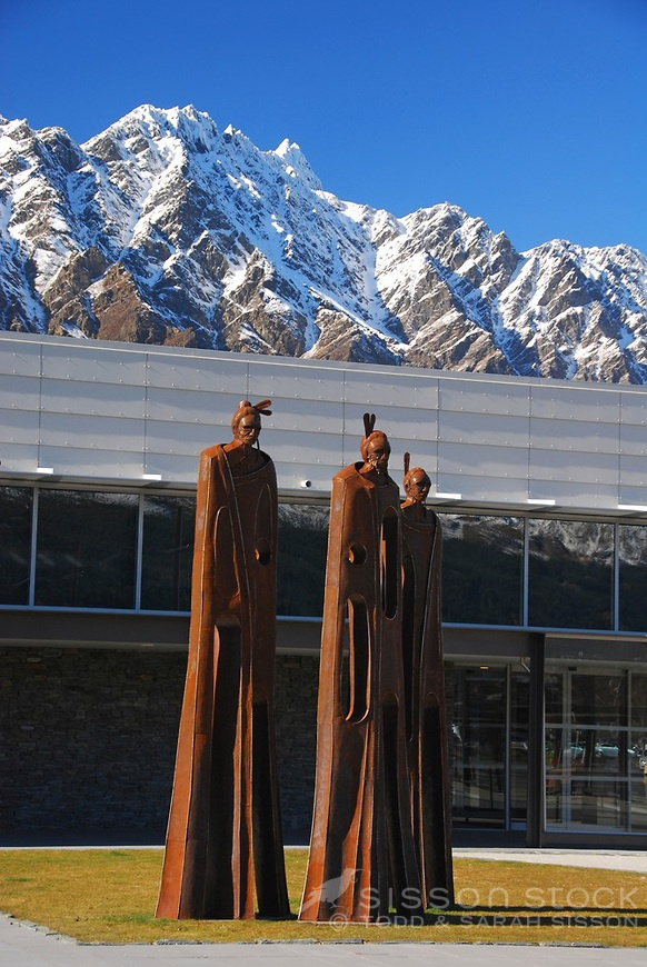 Queenstown Airport Maori Sculpture by Mark Hill with snow clad Remarkables in the background, South Island, New Zealand