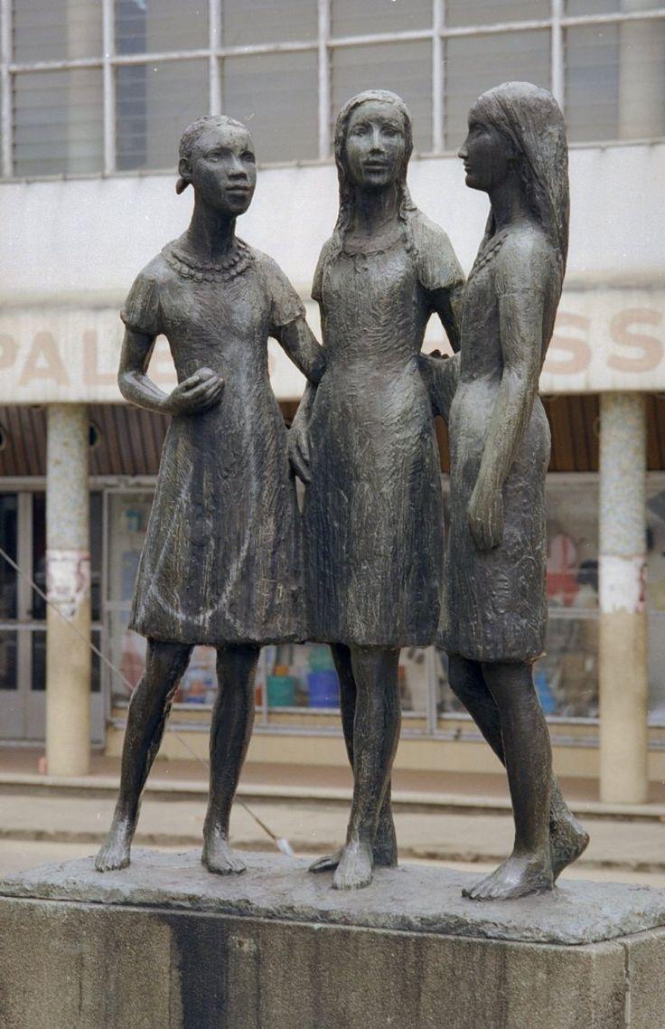 In 1955 onthulde koningin Juliana een monument van dankbaarheid. De drie meisjes staan voor de Creoolse (links) en Hindoestaanse (rechts) Surinamers, die hun armen om de rug van het Nederlandse volk slaan (midden). De opdracht aan de achterkant leest: 'Nederland gedenkt dankbaar de hulp tijdens de oorlog 1940-1945 en daarna door Suriname uit gevoel van saamhorigheid verleend'. Foto: Wikimedia en Rijksdienst voor het Cultureel Erfgoed. Klik foto voor info over Suriname in de Tweede…