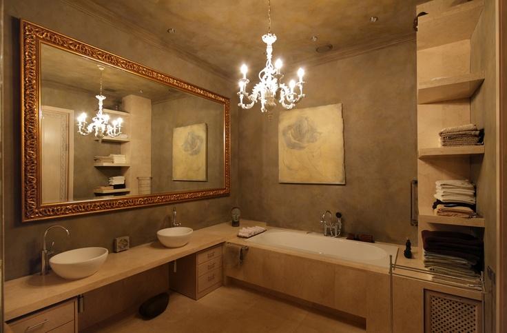 Вдоль бетонных стен ванной — мебель, сделанная на заказ по эскизам Александра. Люстра, Chelini.