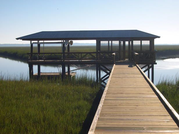 A 230-foot boardwalk stretches over the Georgian marshes and straight to this boat dock at HGTV Dream Home 2004. The covered deck and screened-in living room provide extra entertaining space.