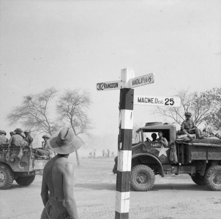 Supply trucks heading south near Pyawbe stop to examine a signpost that points…