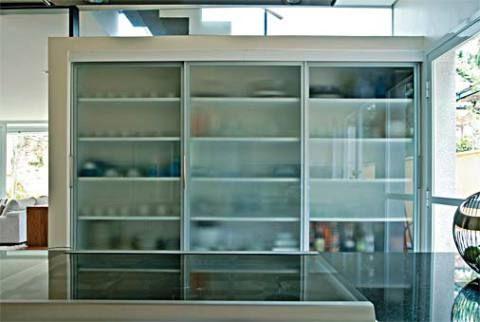 A parede solta separa a sala de jantar da cozinha e se torna um prático armário com prateleiras de MDF e portas de correr de vidro miniboreal (montadas pela Florense). Como a alvenaria não encosta no teto, a luz que vem da caixa da escada transpassa pelo vão superior.