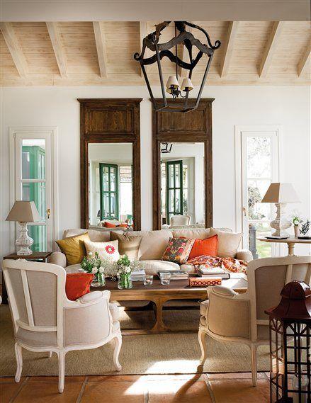 Salón con lámpara de forja y espejos con marcos de madera