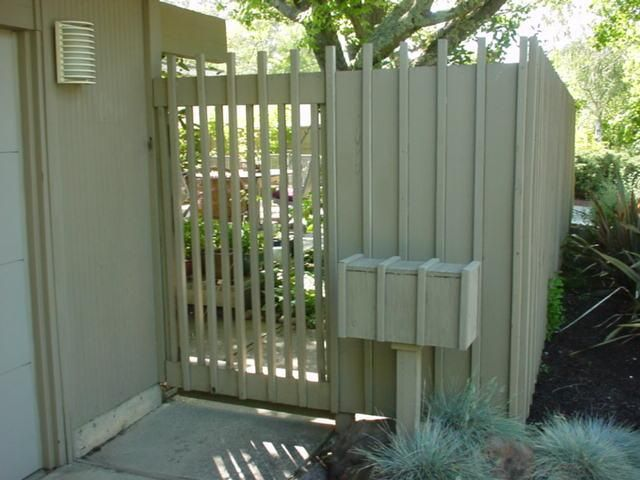 Front Entrance thru a small courtyard.  Narrow Privacy Slats on gate continuing board & batten detail.