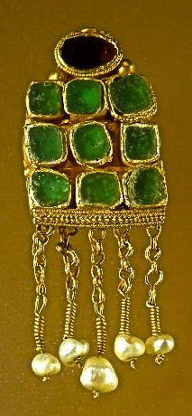 Pendiente con cabujones del siglo VI. Posiblemente romano, de oro, un granate y cristal de colores.