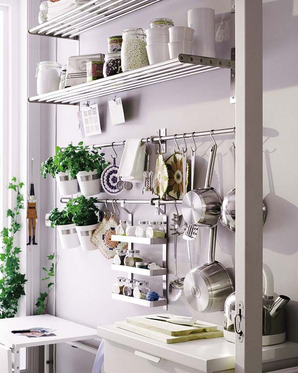 organized kitchen with spices, pots and pans hung with s hooks
