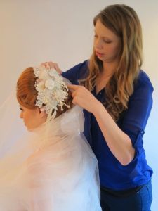 Beverley styling her beautiful bridal headpiece which features lace, draping beadwork and floral elements.