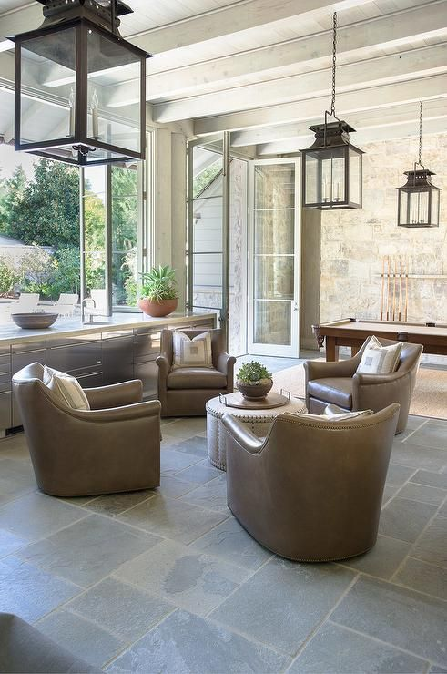 Taupe leather chairs sit in a circular arrangement on concrete pavers around a round burlap ottoman lit by carriage lanterns hung from a white washed plank ceiling accented with wood beams.