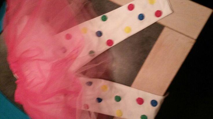 Gekleurde stippen tamponeren  met kurk op witte legging, leuke tule rok erop, shirt met strik en pompons erboven en klaar is je clown outfit! (Tip voor tamponeren; leg een stukje karton in beide pijpen tegen doordrukken van de plakkaatverf)