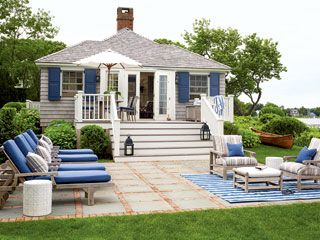 This small deck didn't offer the outdoor living space the homeowners wanted in their Southampton cottage, so they added a bluestone-and-brick patio. Simple wooden furniture with blue-and-white striped details gives this outdoor room a classic, nautical feel.