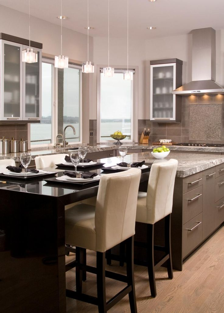 This+contemporary+kitchen+features+a+row+of+pendant+lights,+adding+to+the+natural+light+streaming+in+from+the+large+windows.+White+leather+chairs+pop+against+a+sleek+black+dining+table.+Neutral+granite+countertops+tie+in+tones+used+in+the+cabinetry+and+backsplash.