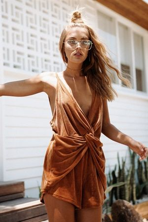 The effortlessly stylish Draped Velvet Playsuit is made from a luscious velvet fabric in a dark tan hue. It has a knot feature which drapes over the hips at front, a deep V neckline and elasticated waistband. Complete the look with neutral flats and a hat! By Sabo Skirt.