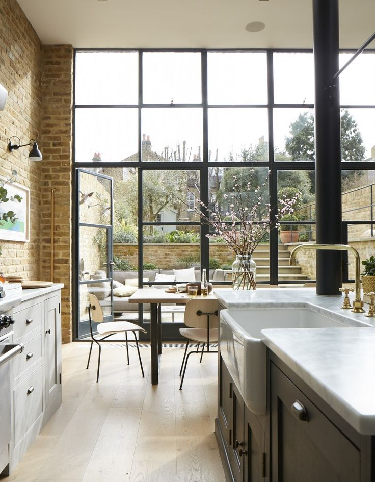 Floor to ceiling windows in this beautiful London home expose the lovely view over the back garden
