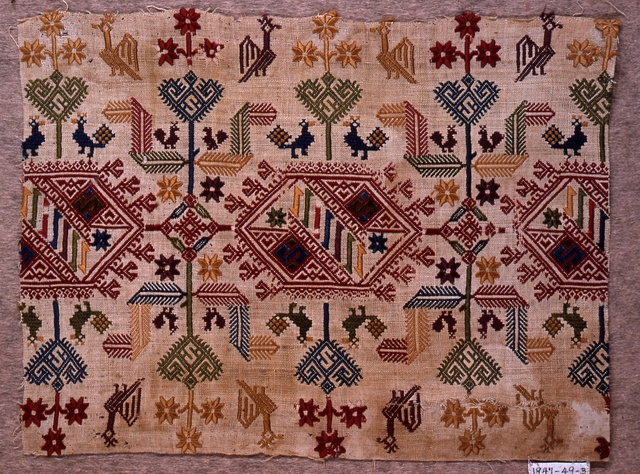 """Design of geometric forms with stylized plants and birds in red, yellow, blue, green and tan on white ground.    This textile is medium: silk embroidery on linen foundation technique: embroidered on plain weave. Its dimensions are: H x W: 19 x 25 cm (7 1/2 x 9 13/16 in.).    This textile is from Greece and dated """"18th century""""."""