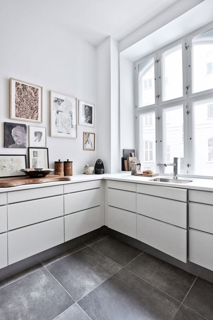 Minimalist white kitchen with large window and art wall | Bo-bedre.no