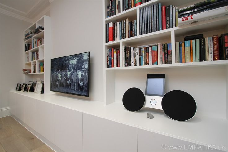 These are contemporary style media wall units built from scratch in London UK by EMPATIKA.uk They are built into alcoves and the base units fit in front of the chimney breast to make a really striking media unit which would not have been the same if there were just units in each alcove. The base units act as a kind of supporting plinth that hold up the bookshelves and highlight the TV. www.EMPATIKA.uk