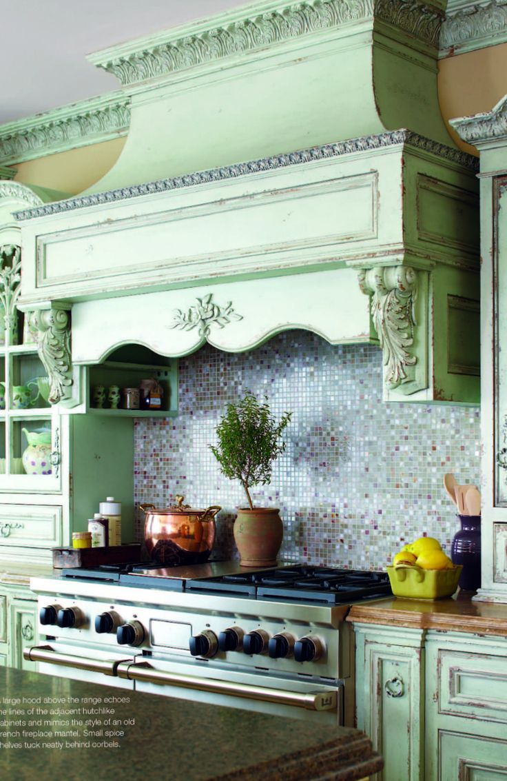"Opulent country-style kitchen. ""The large hood above the range echoes the lines…"